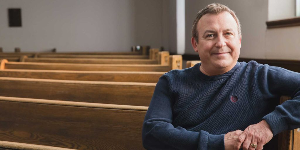 Peter, middle-aged white man, sitting in an empty church, looking at camera.
